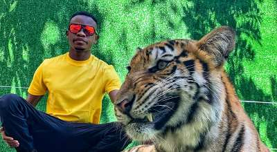 Nigerian pageant King Emmanuel somto poses and chat with a live tiger